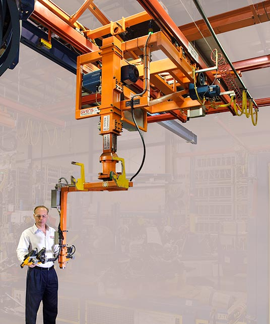 Heavy-duty slide column manipulator for transferring engines from one overhead conveyor to another. Note the blue tractor drive and blue hoist, both made by Demag.
